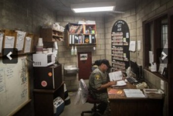 An officer sits in the administrative center of the 4B SHU at Corcoran State Prison. The operating budget of the prison is $192 million per year. – Photo: Grant Slater, KPCC