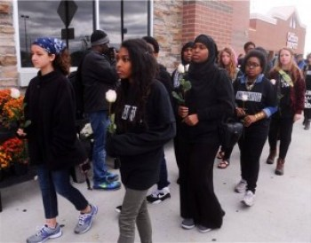 """Youth-led marchers in the John Crawford Pilgrimage embark on their 11-mile walk from the Beavercreek Wal-Mart to the Greene County Courthouse along back roads to, in the words of James Hayes, founding member of the Ohio Student Association, """"show the residents of Greene County, those who are with us and those who are against us, that people are willing to take action in this case."""" – Photo: Marshall Gorby, Dayton Daily News"""