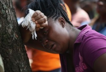 Korpo Klay cries as she watches a Liberian Health Department burial team enter the home of her deceased cousin, Kormassa Kaba, a suspected victim of Ebola.