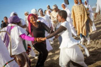 At Maafa 2014, commemorating the African holocaust known as the Middle Passage, not all is somber. Joy radiates from the dancing women and lights up everyone nearby. – Photo: TaSin Sabir
