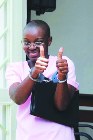 "Victoire Ingabire, despite being in handcuffs for ""genocide denial,"" gives a thumbs up to her supporters outside a Rwandan courtroom on April 17, 2012."