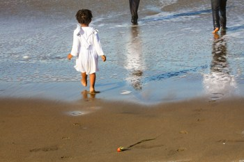 A little girl wades into the ocean following older folk despite the giant waves at Maafa 2014. – Photo: TaSin Sabir