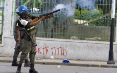 "U.N. troops firing tear gas at Haitian protesters stand in front of a wall with graffiti saying ""Titid,"" Haitians' affectionate name for the forcibly removed elected Haitian President Jean-Bertrand Aristide. – Photo: United Nations Photo"