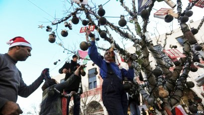 Activists decorate a tree in Manger Square with empty tear-gas grenades. Manger Square lies outside the Church of the Nativity, built on the site of Jesus' birth. – Photo: EPA