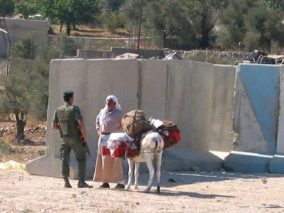 A Palestinian farmer trying to bypass a Bethlehem checkpoint is stopped by an Israeli soldier.