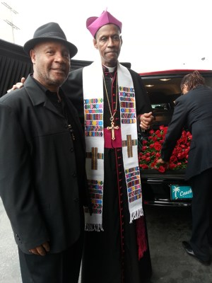 Black Panther Party artist Emory Douglas and Archbishop Franzo King of the Coltrane Church give their last salute to Roland Freeman's casket as it's loaded into the hearse at the Los Angeles funeral for the Freeman brothers. – Photo: JR Valrey, Block Report
