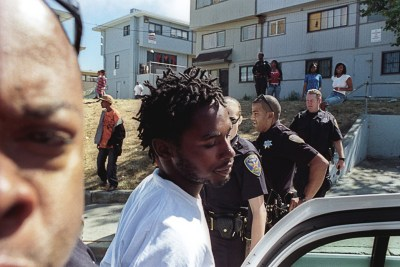 "A young man, Jermaine Jackson, is arrested at Hunters View, one of San Francisco's largest public housing projects, in this 2009 photo. Hunters View is the scene of the city's most dramatic privatization scheme, and in 2009 hundreds of families were fighting eviction, most unsuccessfully. ""With the amount of families in Hunters View dwindling by the month,"" the photographer observes, ""tension between police and the remaining residents runs high."" Occupying police targeted Black youth, who were feared as potential resistance leaders. In this arrest, police claimed they had seen Jackson driving recklessly earlier that day. – Photo: Alex Welsh"