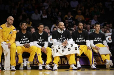 "Lakers, from right, Jeremy Lin, Wayne Ellington, Carlos Boozer, Jordan Clarkson and Nick Young wear ""I can't breathe"" T-shirts as they sit on the bench during the first half of their Dec. 9 game against the Kings. – Photo: Jae C. Hong, AP"