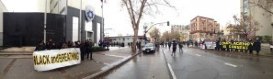 This panoramic view early in the protest shows the Black-led #ShutdownOPD protesters arrayed outside Oakland Police Department Headquarters before a large crowd of supporters had assembled. Four entrances were blocked by non-Black protesters chained together, with lines of chained protesters blocking two streets. Non-Blacks took on the roles that most often lead to arrest, hoping their privileged status would protect them from brutality. It did, and some were not even arrested. – Photo: BaySolidarity