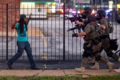 Militarized police threaten a protester in Ferguson on Aug. 11, 2014, two days after Officer Darren Wilson murdered Michael Brown. – Photo: W. Curtis, NY Times