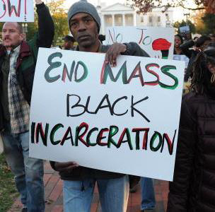 'End Mass Black Incarceration' Black man holding sign at protest