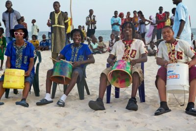 The Senegalese beach crowd waits for the bucket drummers from Chicago to perform.