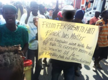 Haiti has been on the march for months. These politically astute protesters make their purpose clear. The face of the person holding the sign has been blurred to protect his identity.
