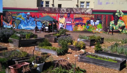 The block-long mural, setting the theme and purpose of AfrikaTown, inspires the work of many hands to grow healthful food to feed the people.