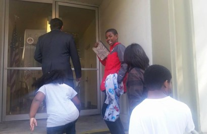 Poverty skolaz from Deecolonize Academy walk into Assemblyman Alejo's office in Salinas, seeking and finding support. Anticipating progress, Kimo James, 12, turns and smiles. – Photo: Poor News Network