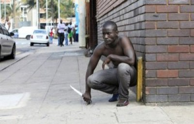 Fearing a xenophobic attack, an immigrant holds tight to his knife on the streets of Durban on April 14. – Photo: AFP