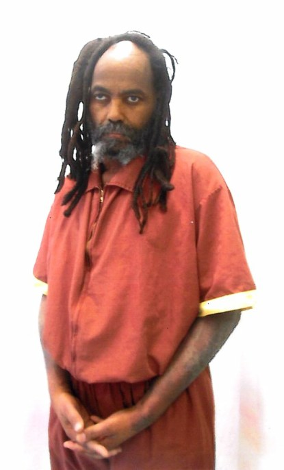 Mumia managed to stand long enough for this photo to be taken on Monday, April 6. He is counting on us to save his life – and bring him home. Note his loss of at least 50 pounds and the dark outbreak on his arms, a painful leathery, bleeding rash that covers much of his body. Please keep calling!
