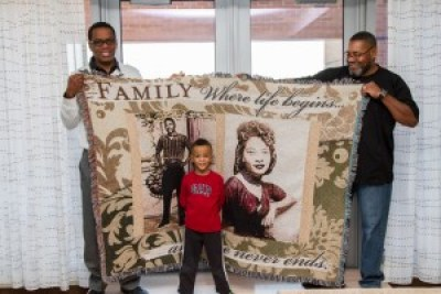 At a reception following the interment in Arlington National Cemetery, Carlos Mitchell and Woodrow Cameron, grandsons-in-law of Wyley and Ouida Wright, and a great-grandson show a tapestry picturing the Wrights as young adults presented by Greene Funeral Home. – Photo: Andre Thompson courtesy Ray Caling