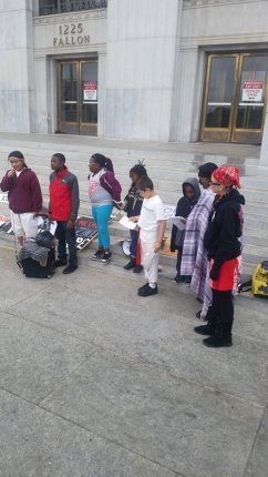 "Youth skolas of Deecolonize Academy in Deep East Oakland line up to speak at the anti-eviction rally outside ""Eviction Kkkort,"" the Alameda County Courthouse, site of many Black Panther demonstrations back in the day. – Photo: Poor News Network"