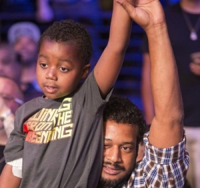 Andre Ward's victory salute to his fans is returned by a young fan and his father.  – Photo: Malaika Kambon