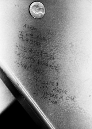 "This is the entire message that Aaron scratched on the underside of a bench as he was being tortured: ""Aaron – I lie about murders. Police threaten me with violence, slapped and suffocated (illegible) plastic. No lawyer or (illegible). No phone."""