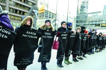 "Called ""Chicago shows love to Jon Burge torture victims,"" supporters staged a dramatic demonstration in the snow on Feb. 14, 2015, as Chicago deliberated reparations. The long line named 118 victims, including Aaron Patterson. – Photo: Sarah Jane Rhee"