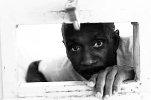 A prisoner in solitary confinement in the Louisiana State Penitentiary Angola, a former plantation, peers through his mail and food slot. Will the condemnation of longterm solitary by Justice Kennedy and President Obama help him finally find freedom? – Photo: Adam Shemper