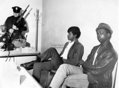 """The photographer's caption reads """"Black Panthers Bobby Seale and Bobby Hutton detained at the Oakland Police Dept. while officers check guns. Hutton was shot and killed by police shortly after this photo when he and Eldridge Cleaver were involved in a shoot-out with Oakland Police. (1967 photo by Ron Riesterer)"""" Actually, Lil Bobby Hutton, the first person to join the Black Panther Party shortly after its founding in October 1966, when he was only 15, was killed on April 6, 1968, two days after Martin Luther King was assassinated."""