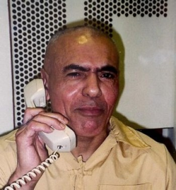 "Hugo ""Yogi"" Pinell talks with a visitor in 2001 on the phone at Pelican Bay State Prison – thick glass in a concrete wall dividing them. Through his decades in Pelican Bay, he was never able to touch a visitor or any friendly person."