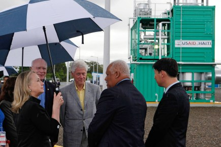 "Then-Secretary of State Hillary Clinton is joined by her husband, former U.S. President Bill Clinton, and Sen. Pat Leahy at a new power plant during their visit to Caracol, Haiti, in 2012. This photo illustrates a Wall Street Journal article headlined: ""How the Clintons Worked the Angles in Haiti: Bill handled earthquake aid while Hillary was secretary of state; the nation deserved better."" – Photo: Larry Downing, AFP"