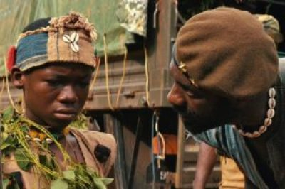 "Idris Elba plays the leader of an African militia that takes in a boy played by Abraham Attah and teaches him to be a soldier in the Netflix film, ""Beasts of No Nation."" – Photo: Netflix"