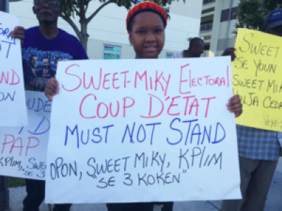 "Protesters outside a Haitian presidential debate in Miami on Oct. 4 denounce the Aug. 9 ""electoral coup."" – Photo: Haiti Information Project"