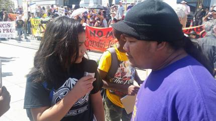 Kimo Umu, a student at Deecolonize Academy, interviews Raymond Castillo of SOMCAN, a leading opponent of the 5M project at one of many large protests. – Photo: Poor News Network