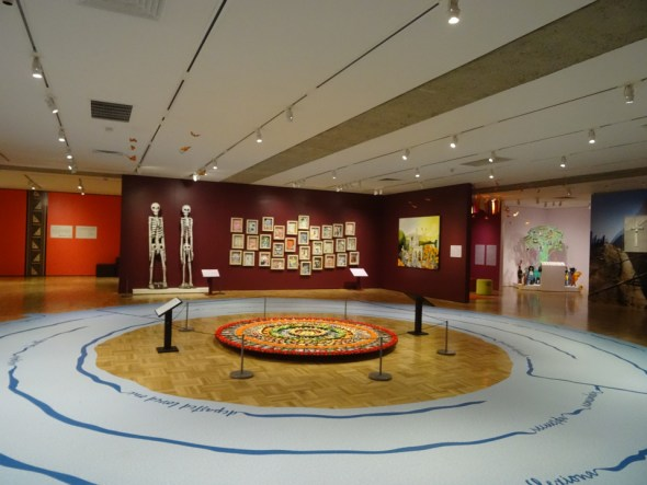 """In this view of the Oakland Museum gallery featuring the Dia de los Muertos exhibit, the story tree in the back right corner has recorded stories by high school youth recalling their ancestors and talking about their ancestry, along with headphones for visitors to listen. """"I listened to all their stories,"""" Wanda says. – Photo: Wanda Sabir"""