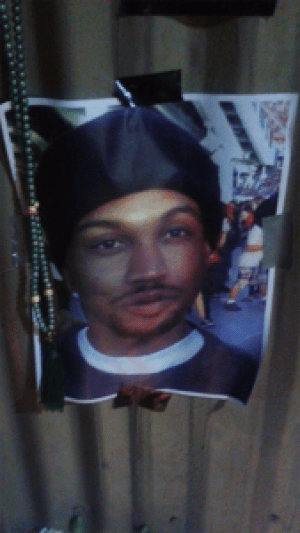 Mario Woods' picture is posted to the wall behind his memorial, built on the sidewalk where he was executed.