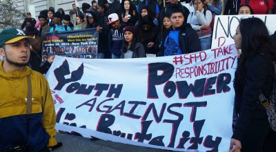 Hundreds of students, who walked out of class and marched from 16th and Mission to City Hall, unfurled their banner and rallied on the steps, as a cop in the background stood watch. – Photo: Paulette Justice