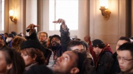 In another part of the vast City Hall rotunda, protester Charles Pitts starts a chant. – Photo: Noé Serfaty