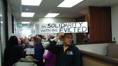 Peaceful protestors go to speculator Quan He's attorney's office to call on him to honor their agreement to give Pastor Dorn more time to untangle the snafu caused by Chase Bank and keep his family in their home of 20 years. Supporter and community activist Hanson Lee holds a sign explaining their mission. – Photo: Grace Martinez