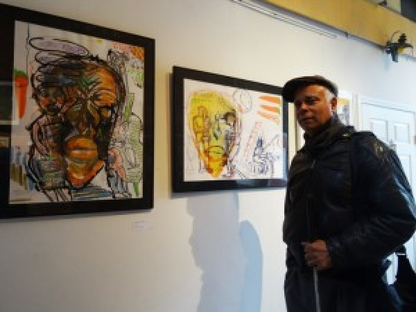 "Charles Curtis Blackwell stands in front of his work at Warehouse 416, where ""Invisible Black Men"" is up through Feb. 28. – Photo: Wanda Sabir"