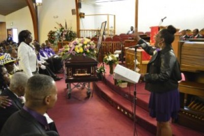 Mother Jackson's granddaughter, De Trice Rogers, reads the obituary and her grandmother's accomplishments. – Photo: Patricia Winston