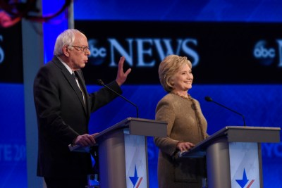Sen. Bernie Sanders speaks as former Secretary of State Hillary Clinton smiles during an ABC News debate in December. – Photo: Disney, ABC