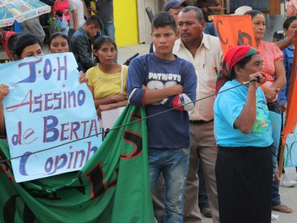 "In La Esperanza, an Indigenous woman holds a sign reading ""JOH (Juan Orlando Hernandez), Assassin of Berta, COPINH."" Tens of thousands have taken to the streets throughout the month. – Photo: Jeanette Charles"
