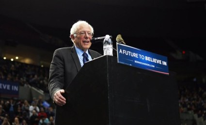 "Something miraculous happened during Bernie's rally in Portland on March 25, 2016. A tiny bird, a finch, flew down to land on the stage by Bernie's feet. When he noticed the little bird, it hopped up onto the lectern and looked intently at him for quite a while, as Bernie told the crowd that the bird – a messenger perhaps? – ""is asking us for world peace, no more wars!"" – Photo: The Portland Oregonian"