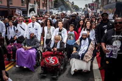 On May 3, the 13th day of their hunger strike, the Frisco 5, in wheelchairs pushed by the doctors and medical students who have been monitoring their health, march with a thousand supporters to City Hall for a showdown with Mayor Ed Lee, who ducked out. Ike Ali Pinkton is just out of camera range at the left. Selassie Blackwell was hospitalized the next day but was soon back with his comrades. – Photo: Mona Caron