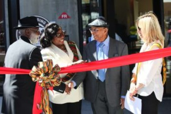 It was a day of greetings and the strengthening of bonds between friends, colleagues and neighbors. Dr. Aurelious Walker, pastor of True Hope Church of God in Christ and a speaker at the grand opening, shakes hands with Bay View publisher Dr. Willie Ratcliff as Dr. Carolyn Ransom-Scott and Nancy Pike (far right) look on approvingly. – Photo: PhotoArtist Gene Hazzard