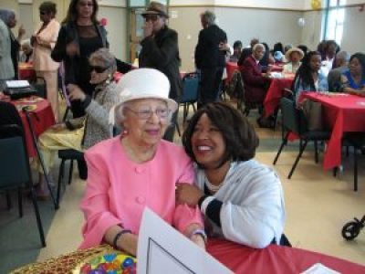 Amid the happy throng celebrating her 100th birthday at Jones Methodist on June 12, Ms. Pickens gets a special hug from her granddaughter, Charisse. – Photo: Anh Le