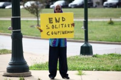 Sister Linda Muhammad holds a sign during the rally outside the state Department of Corrections headquarters in Madison to protest long-term solitary confinement. Her son, Robert Tatum, was being held in disciplinary solitary confinement at Waupun Correctional Institution. – Photo: Coburn Dukehart, Wisconsin Center for Investigative Journalism