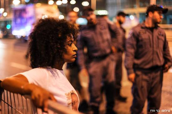 Ethiopian-Israeli activist Tehune Maharat, cousin of the late Yosef Salamsa, takes in the Tel Aviv protest, as uniformed police officers look on. – Photo: Benny Woodoo