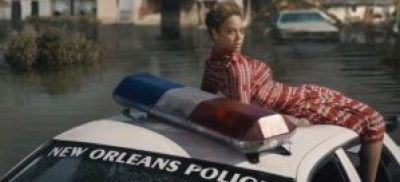 "The symbolism is heavy in this shot from the ""Formation"" video showing Beyonce atop a New Orleans police car partially submerged in the flood."