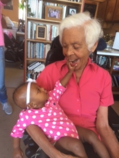 Revolutionary journalist Kiilu Nyasha enjoys a young visitor, Aaliyah Robinson, daughter of Nia Sykes, granddaughter of Ida McCray.